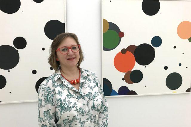 Kurátorka výstavy Markéta Kroupová před obrazem Zdeňka Sýkory, Barevné nulové linie, 2011, serigrafie na papíru