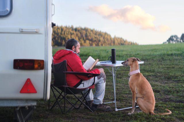 Muž a pes u karavanu